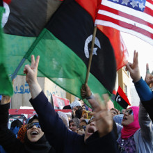 Protesters hold Kingdom of Libya flags and an American flag during an anti-Gaddafi demonstration in Benghazi