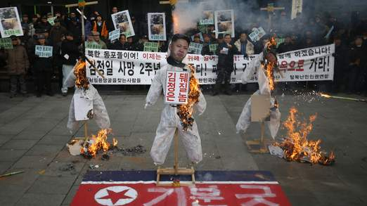 Effigies of North Korean founder Kim Il Sung, leader Kim Jong Un and former leader Kim Jong Il are set on fire by protesters during an anti-North Korean rally in central Seoul