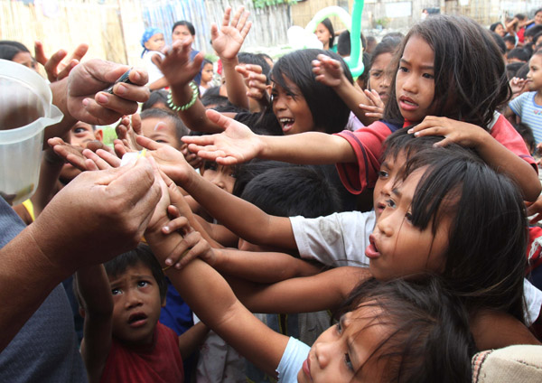 Children reach their hands to get a stub for a free meals during a feeding program donated by a South Korean missionary in a slum area at Baseco, Tondo city, metro Manila