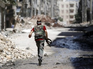 A Free Syrian Army fighter runs during clashes with Syrian Army in the Salaheddine neighbourhood of central Aleppo