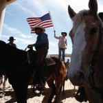 A protester waves the U.S. flag near the Bureau of Land Management's base camp where seized cattle, that belonged to rancher Cliven Bundy, are being held at near Bunkerville