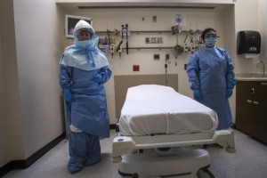 Health care workers display protective gear, which hospital staff would wear to protect them from an Ebola virus infection, inside an isolation room as part of a media tour of the emergency department of Bellevue Hospital in Manhattan