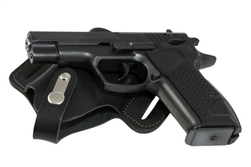 The automatic pistol lays on holser black color.
