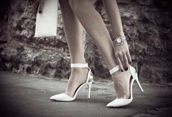 woman legs in elegant white high heel shoes outdoor shot in the city summer day