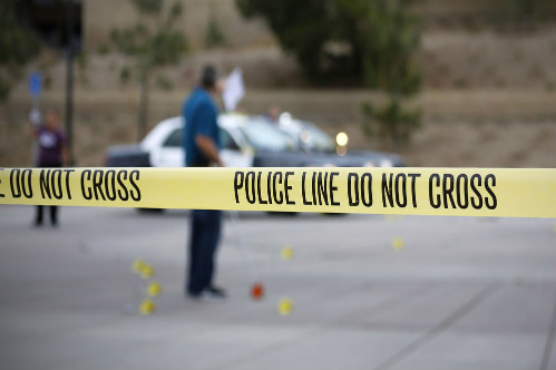 A member of the San Diego Police Department investigates the scene of a fatal police officer involved shooting of a 15-year-old boy in one of the parking lots in front of Torrey Pines High School, early Saturday morning. Photo Credit: San Diego Union Tribune