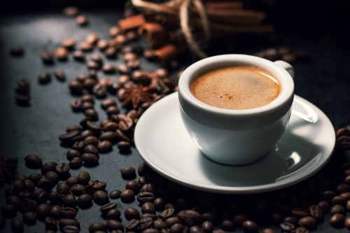 Fresh tasty espresso cup of coffee with coffee beans on dark background